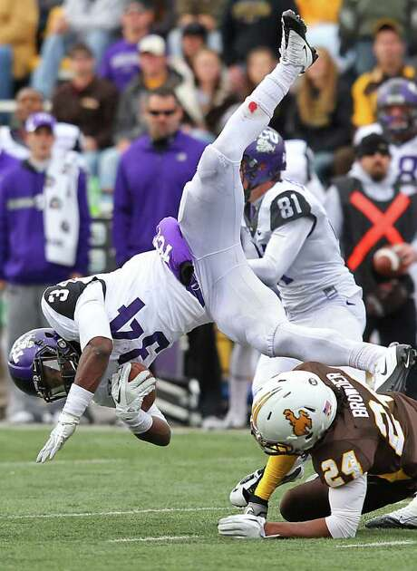 MICHAEL SMITH: ASSOCIATED PRESS LEAPING FROG: Wyoming's Kenny Browder knocks TCU's Ed Wesley, who rushed for 120 yards, off his feet. Photo: Michael Smith / Wyoming Tribune Eagle