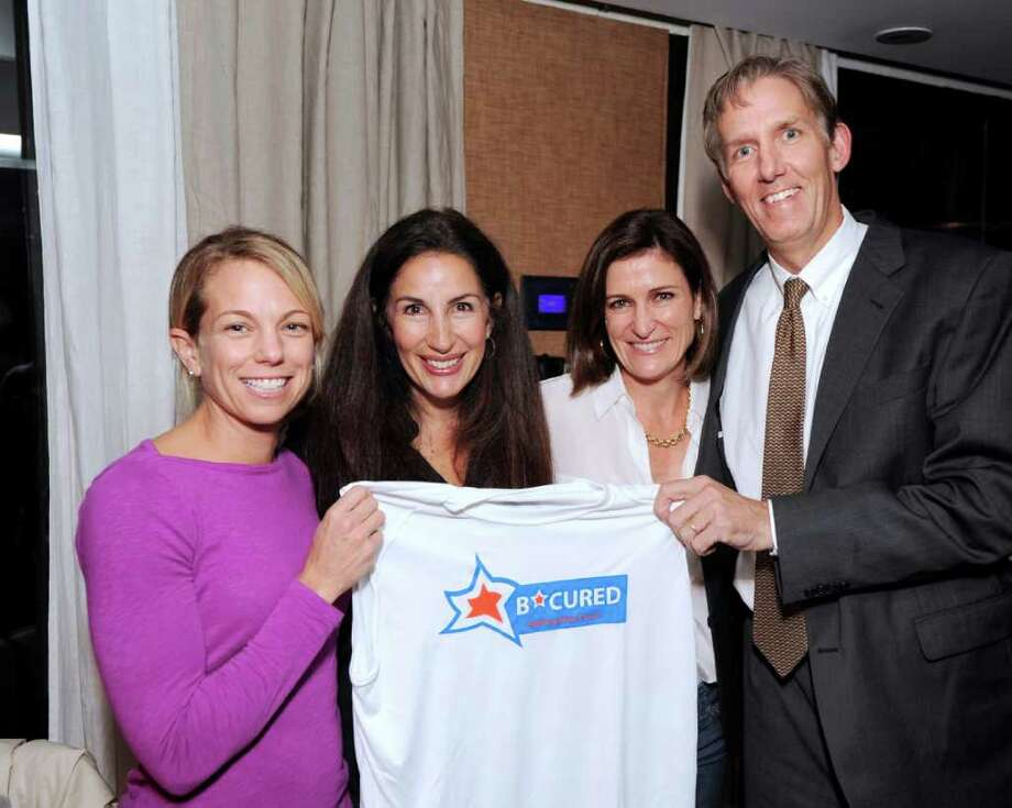 From left, Tara Allen, Debbie Needle, Melissa Salame and Dick Taggart, all of Greenwich pose with a B*Cured team T-shirt during a team get-together at Barcelona Restaurant in Greenwich Thursday night, Oct. 27, 2011. Allen and Taggart will be running in the New York City Marathon to raise money for the B*Cured Foundation, started by founders Needle and Salame.  The organization raises money for brain cancer research with the hope of finding a cure. Photo: Bob Luckey / Greenwich Time