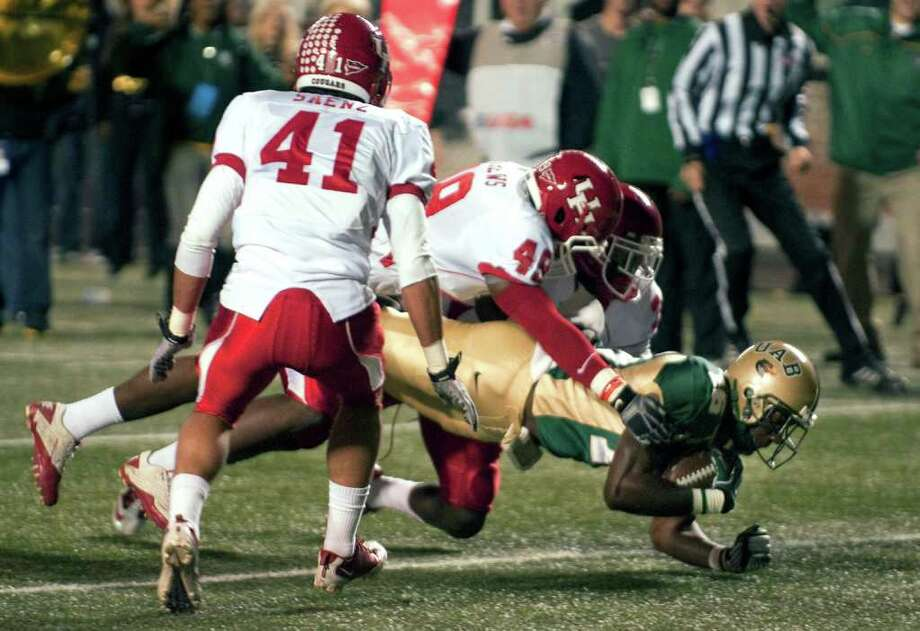 UAB's Patrick Hearn, bottom right, scores as he is brought down by Houston's Derrick Mathews (49) in the first half of an NCAA college football game, in Birmingham, Ala., Saturday, Nov. 5, 2011. (AP Photo/Bob Farley) Photo: Bob Farley, Associated Press / FR44186 AP