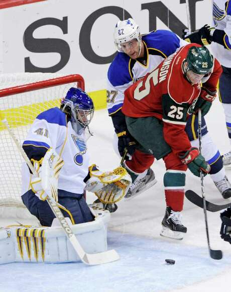 JIM MONE: ASSOCIATED PRESS IN THE CREASE: The  Wild's Nick Johnson (25) tries to coax a backhand past  Blues goalie Jaroslav Halak. Photo: Jim Mone / AP