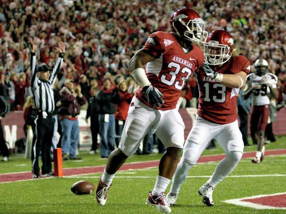 DAVID QUINN: ASSOCIATED PRESS SPECIAL MOMENT: Arkansas' Dennis Johnson, left, and Seth Armbrust celebrate Johnson's 98-yard kickoff return for a touchdown. Photo: David Quinn / FR74919 AP