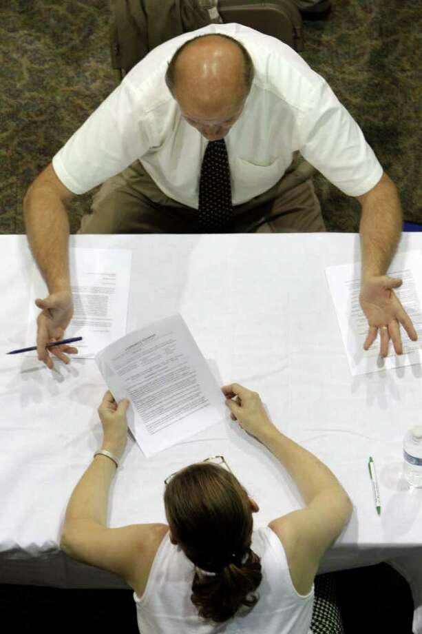 FILE - In this Aug. 25, 2010 file photo, a job applicant receives advice on his resume while attending a job fair in Southfield, Mich. Nearly all states provide up to 26 weeks of unemployment benefits. During the recession, Congress added up to 73 extra weeks in states with especially high unemployment. As a result, up to 99 weeks of benefits are available in 22 states and up to 93 weeks in four other states.  (AP Photo/Paul Sancya, file) Photo: Paul Sancya