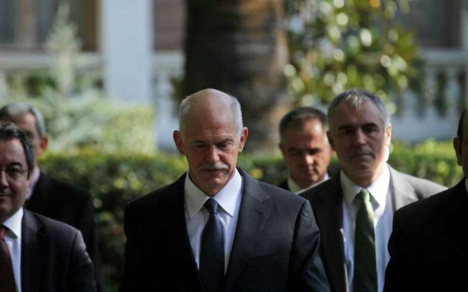 Greece's Prime Minister George Papandreou exits Presidential house after meeting with Greek President Karolos Papoulias,  in Athens on Saturday, Nov. 5, 2011. Embattled Greek Prime Minister George Papandreou launched efforts to form a four-month coalition government, arguing the move is vital to demonstrating Greece's commitment to remaining in the eurozone.(AP Photo/Kostas Tsironis) Photo: KOSTAS TSIRONIS / AP