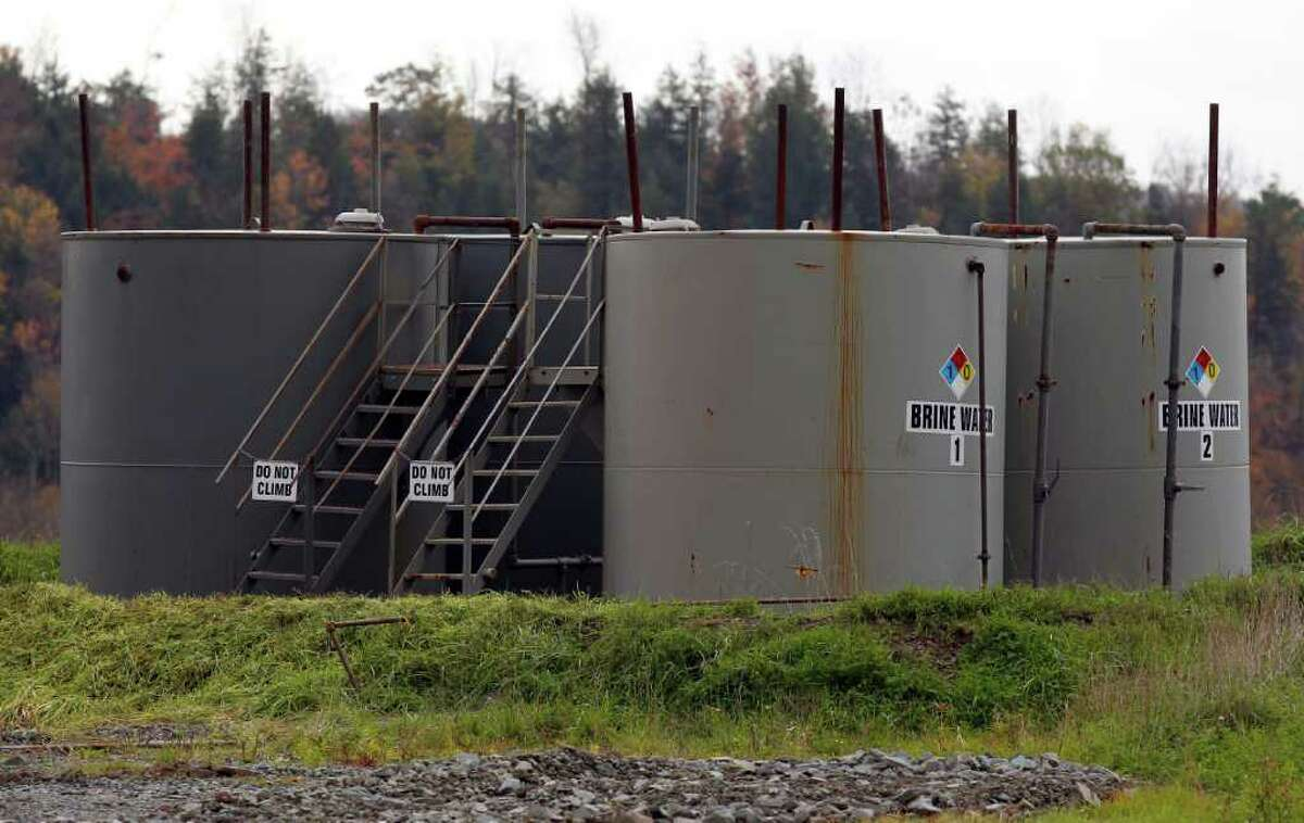 Tanks of tainted water used in natural gas hydrofracking stand next to a gas well in Dimock, Pa. An alternative technology developed in Canada does away with pumping millions of gallons of water to break up underground gas-bearing rocks, and replaces it with a gelled propane. (Alex Brandon / AP)