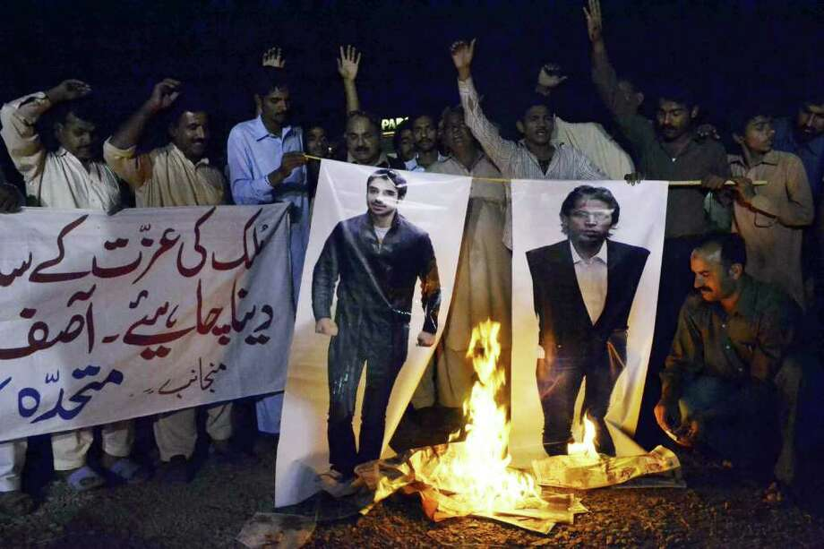 S.S. MIRZA : AFP / GETTY IMAGES SPURNED, BURNED: Pakistanis burn photos of cricketers Salman Butt and Mohmmad Asif during a protest in Multan. Photo: S.S. MIRZA / AFP