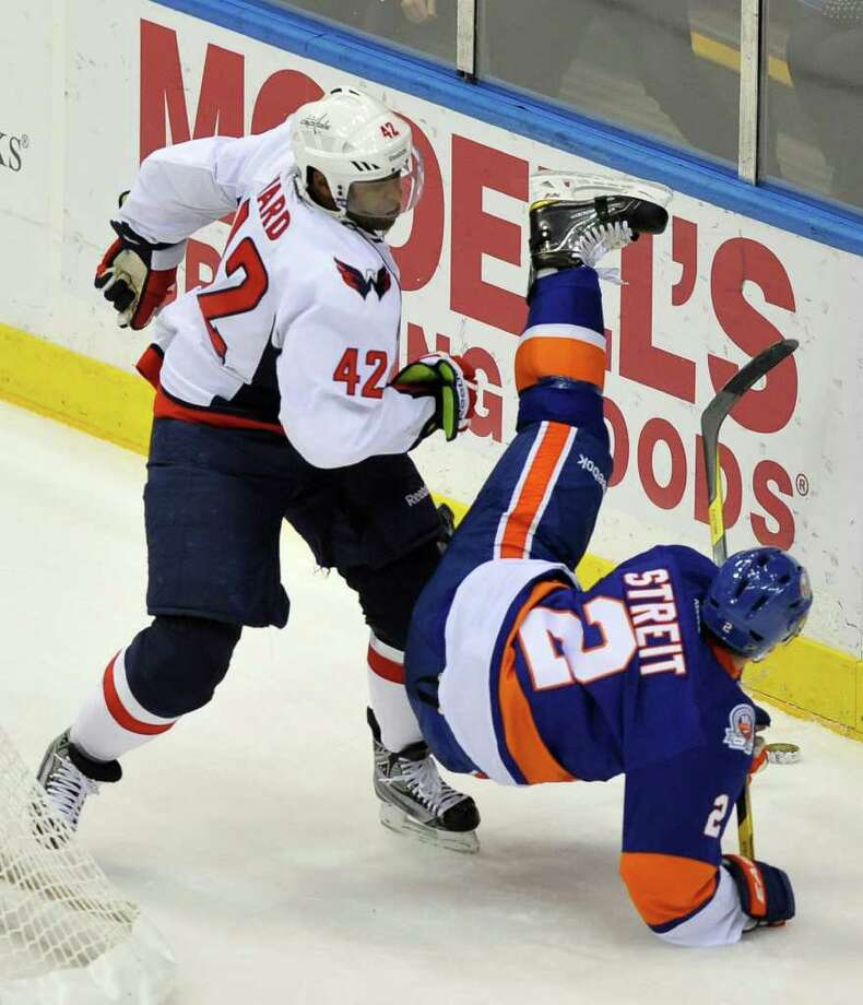 New York Islanders' Mark Streit (2) falls to the ice after colliding with Washington Capitals' Joel Ward (42) during the first period of an NHL hockey game on Saturday, Nov. 5, 2011, in Uniondale, N.Y. (AP Photo/Kathy Kmonicek) Photo: Kathy Kmonicek