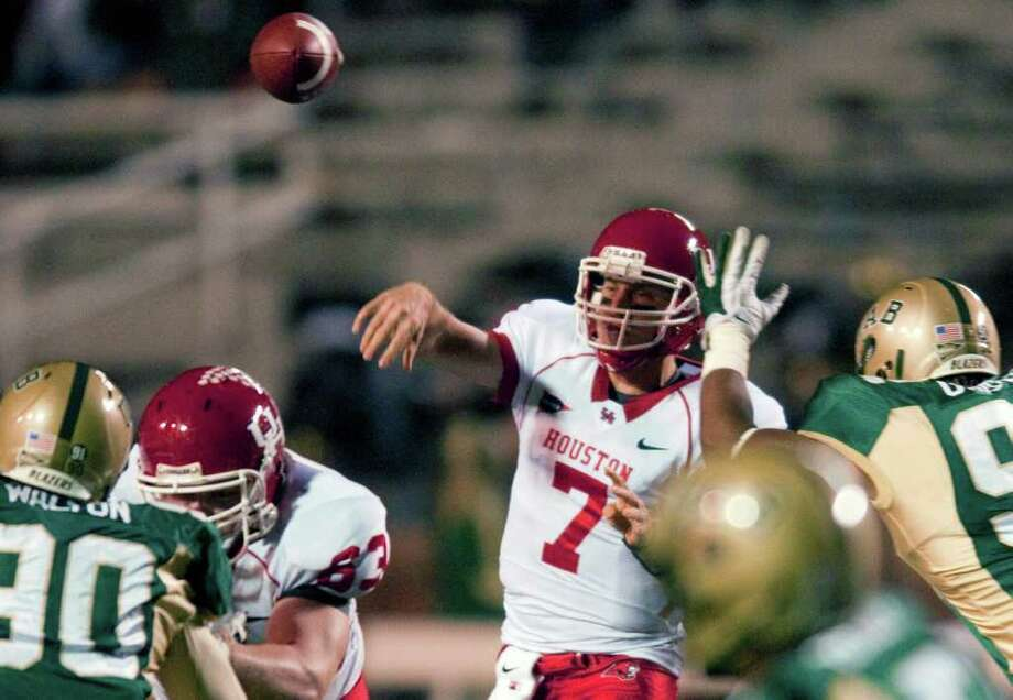 Bob Farley: Associated Press AIR TO THE THRONE: UH quarterback Case Keenum, center, had 407 yards passing Saturday night to move into the top spot on the NCAA's career list. Photo: Bob Farley / FR44186 AP