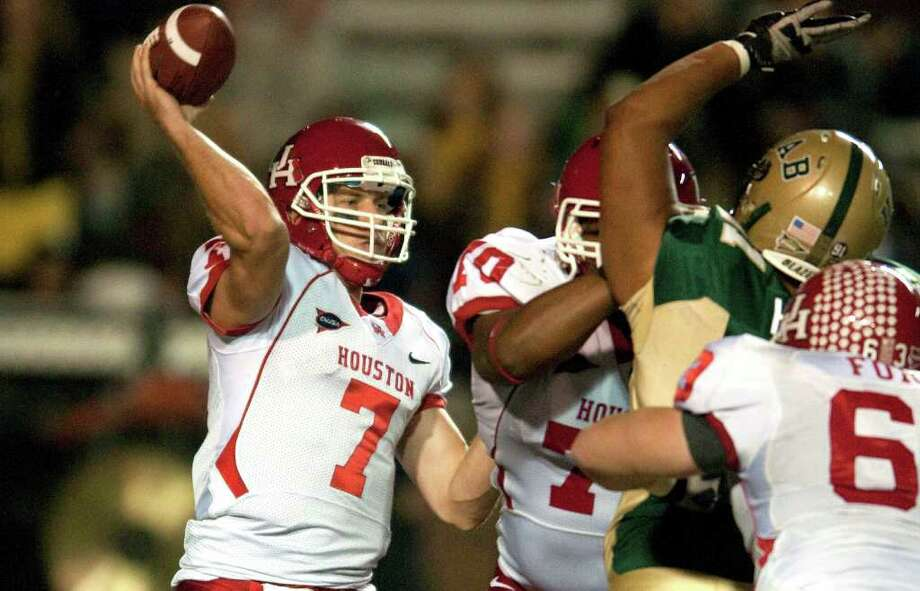 While UH quarterback Case Keenum, left, is breaking records, the Cougars are still focused on getting to the C-USA Championship game. Photo: Bob Farley / AP