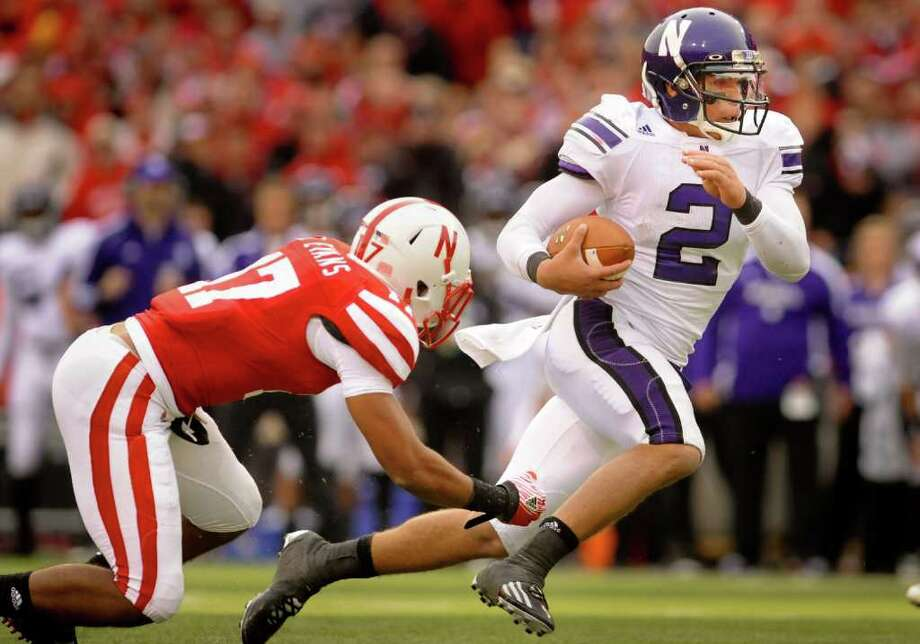 Northwestern's Kain Colter (2) slips by Nebraska's Ciante Evans (17) during an NCAA football game, Saturday Nov. 5, 2011, in Lincoln, Neb. (AP Photo/Dave Weaver) Photo: Dave Weaver