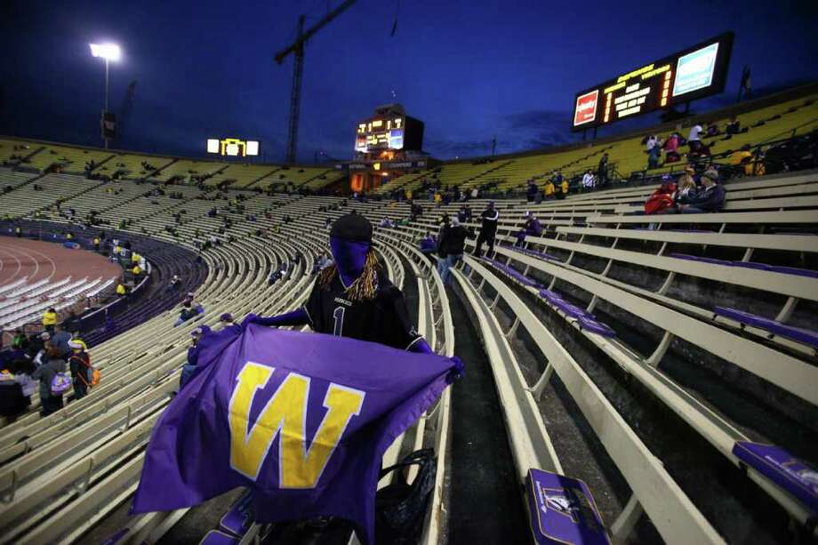 Trevor Mascarenas, 17, from Stanwood, unfurls his Husky flag at Husky Stadium before a game against the Oregon Ducks on Saturday, November 5, 2011. The game was the last to be held at the aging stadium. Beginning next week demolition of the stadium will begin. Photo: JOSHUA TRUJILLO / SEATTLEPI.COM