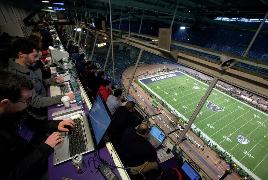 Reporters work high overhead in the press box at Husky Stadium during a game against the Oregon Ducks on Saturday, November 5, 2011. The game was the last to be held at the aging stadium. Beginning next week demolition of the stadium will begin. Photo: JOSHUA TRUJILLO / SEATTLEPI.COM