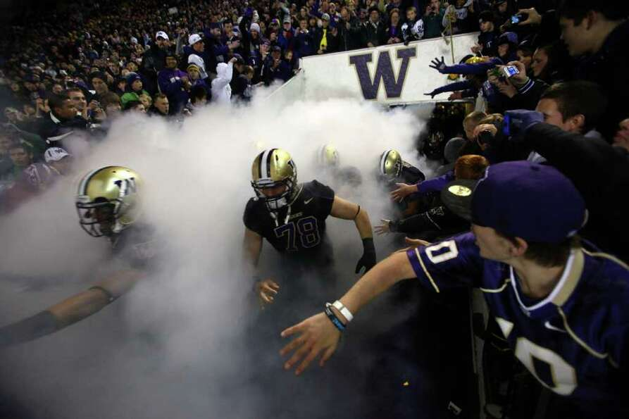 Football players take the field at Husky Stadium during a game against the Oregon Ducks on Saturday,