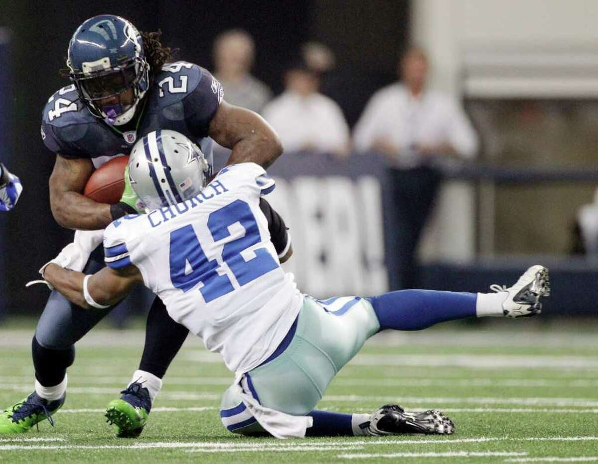 Dallas Cowboys defensive back Barry Church (42) tackles Seattle Seahawks' Marshawn Lynch (24) during the first half of an NFL football game on Sunday, Nov. 6, 2011, in Arlington, Texas.