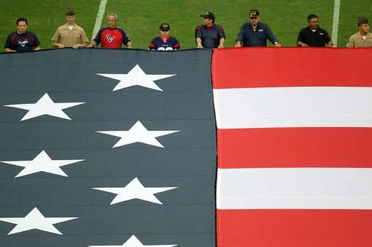 US military veterans hold a large American flag in the shape of the United States as it is unfurled before the Houston Texans play the Cleveland Browns in an NFL football game at Reliant Stadium on Sunday, Nov. 6, 2011, in Houston. Photo: Smiley N. Pool, Houston Chronicle / © 2011  Houston Chronicle