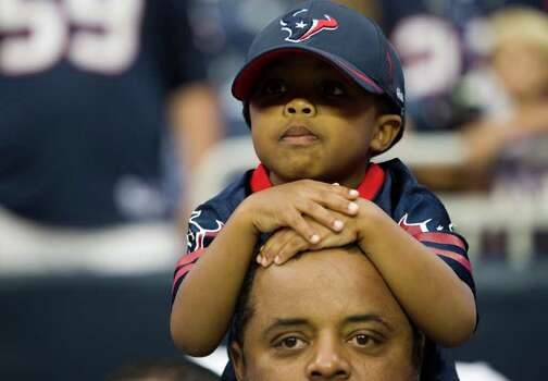 Houston Texans fan Christopher Martin sits atop his uncle Roland Martin's shoulders before an NFL football game against the Cleveland Browns at Reliant Stadium on Sunday, Nov. 6, 2011, in Houston. Photo: Brett Coomer, Houston Chronicle / © 2011  Houston Chronicle