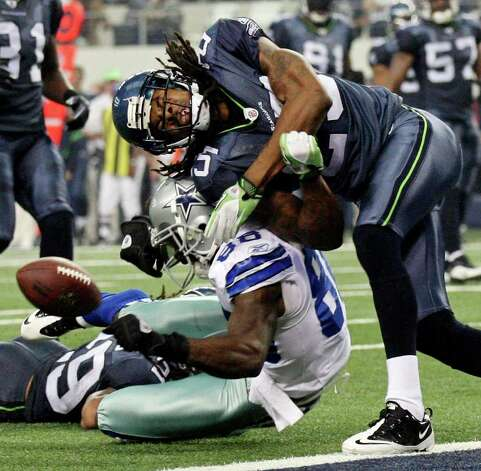 Dallas Cowboys' Dez Bryant fumbles the ball after being hit by Seattle Seahawks' Richard Sherman during first half action Sunday Nov. 6, 2011 at Cowboys Stadium in Arlington, TX. EDWARD A. ORNELAS/eaornelas@express-news.net / © SAN ANTONIO EXPRESS-NEWS (NFS)
