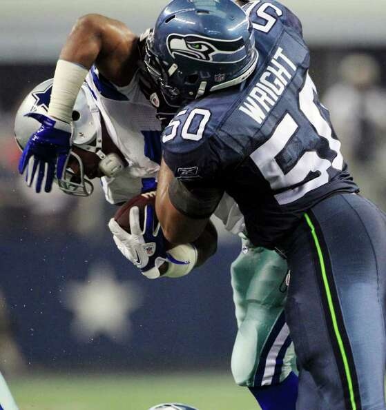 Dallas Cowboys' Phillip Tanner, left, is tackled by Seattle Seahawks outside linebacker K.J. Wright