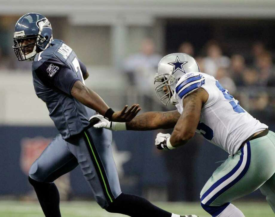 Seattle Seahawks' Tarvaris Jackson, left, deflects Dallas Cowboys outside linebacker Anthony Spencer during the first half of an NFL football game on Sunday, Nov. 6, 2011, in Arlington, Texas. Photo: AP
