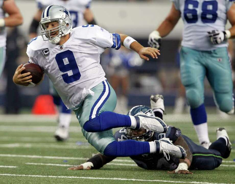 Dallas Cowboys' Tony Romo (9) rushes for a first down against the Seattle Seahawks during second half of an NFL football game on Sunday, Nov. 6, 2011, in Arlington, Texas. Seahawks' Anthony Hargrove defends. Photo: AP