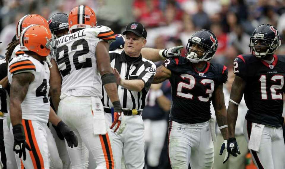 Field judge Scott Steenson (88) stands between Houston Texans and Cleveland Browns players during th