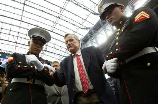 Former President George H.W. Bush is helped onto the field to flip the coin before an NFL football game between the Houston Texans and the Cleveland Browns at Reliant Stadium on Sunday, Nov. 6, 2011, in Houston. Photo: Brett Coomer, Houston Chronicle / © 2011  Houston Chronicle
