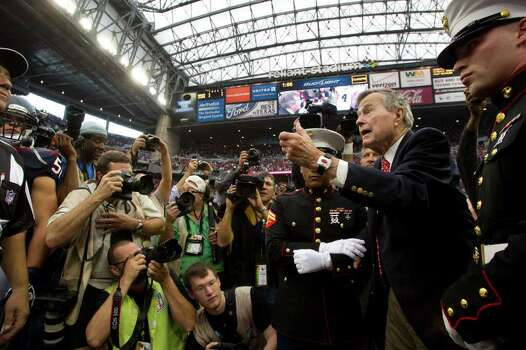 Former President George H.W. Bush flips the coin before an NFL football game between the Houston Texans and the Cleveland Browns at Reliant Stadium on Sunday, Nov. 6, 2011, in Houston. Photo: Brett Coomer, Houston Chronicle / © 2011  Houston Chronicle