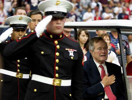 Former President George H.W. Bush puts his hand on his heart during the national anthem before an NFL football game between the Houston Texans and the Cleveland Browns at Reliant Stadium on Sunday, Nov. 6, 2011, in Houston. Photo: Brett Coomer, Houston Chronicle / © 2011  Houston Chronicle
