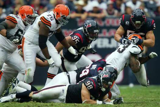 Houston Texans inside linebacker Brian Cushing (56) and defensive end J.J. Watt (99) bring down Cleveland Browns running back Thomas Clayton (33) during the third quarter of an NFL football game at Reliant Stadium on Sunday, Nov. 6, 2011, in Houston. Photo: Smiley N. Pool, Houston Chronicle / © 2011  Houston Chronicle