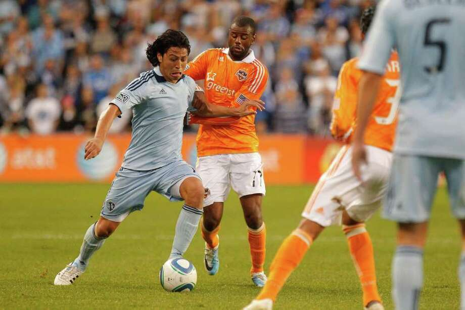 KANSAS CITY, KS - NOVEMBER 06:  Roger Espinoza #15 of the Sporting Kansas City attemps to fight past the defense of Luiz Camargo of the Houston Dynamo in the first half during the MLS Eastern Conference Championship match at Livestrong Sporting Park on November 06, 2011 in Kansas City, Kansas. Photo: Kyle Rivas, Getty / 2011 Getty Images