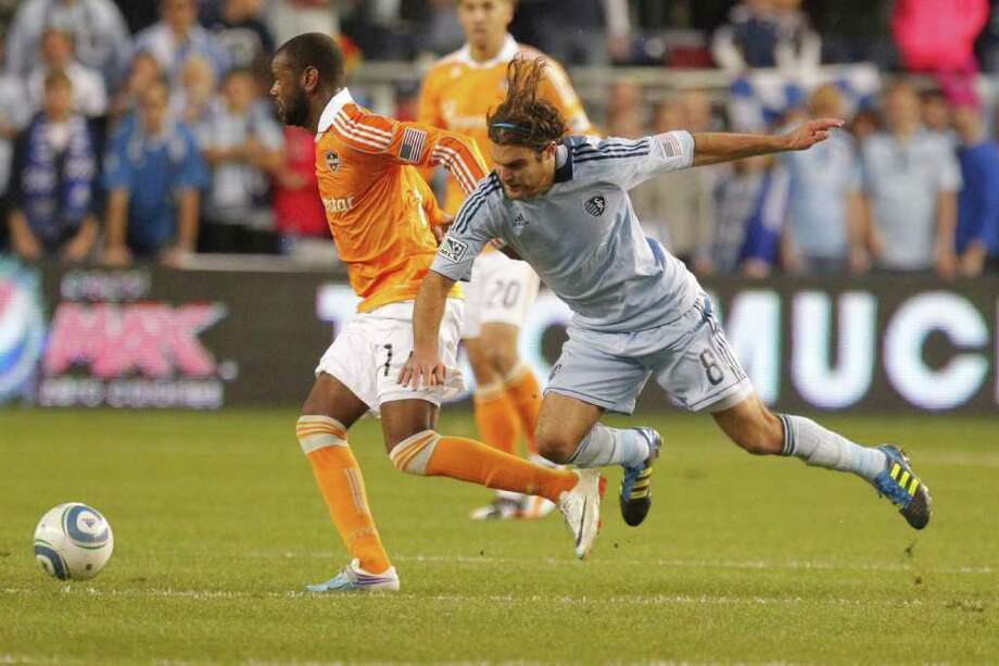 KANSAS CITY, KS - NOVEMBER 06:  Graham Zusi #08 of the Sporting Kansas City trips while defending Luiz Camargo #17 of the Houston Dynamo in the second half during the MLS Eastern Conference Championship match at Livestrong Sporting Park on November 06, 2011 in Kansas City, Kansas. Photo: Kyle Rivas, Getty / 2011 Getty Images