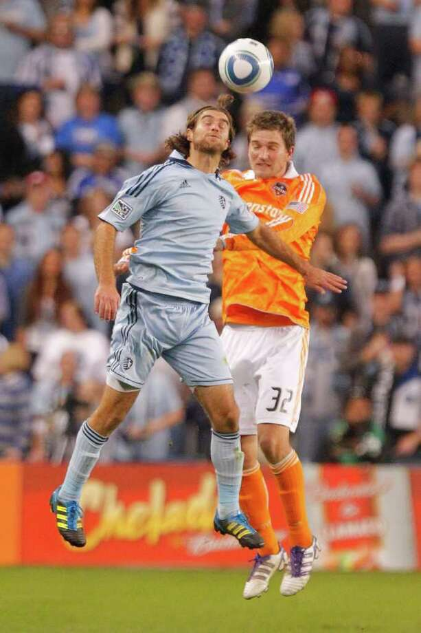 KANSAS CITY, KS - NOVEMBER 06:  Graham Zusi #08 of the Sporting Kansas City and Bobby Boswell #32 of the Houston Dynamo attempt to gain control of a header in the first half during the MLS Eastern Conference Championship match at Livestrong Sporting Park on November 06, 2011 in Kansas City, Kansas. Photo: Kyle Rivas, Getty / 2011 Getty Images