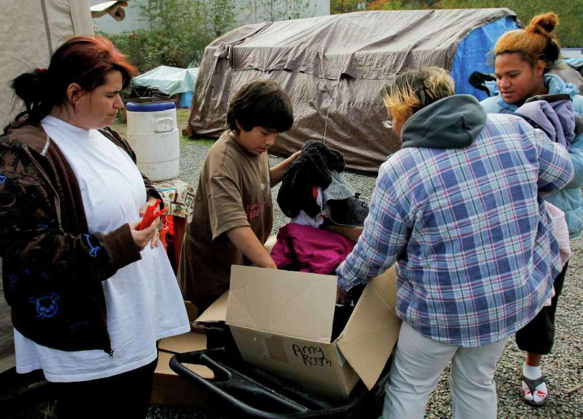 K'eet Dundas, 11, sorts through some newly donated clothing at the Nickelsville tent community in West Seattle on Sunday Nov. 6, 2011. The clothing came from a girl who passed away.