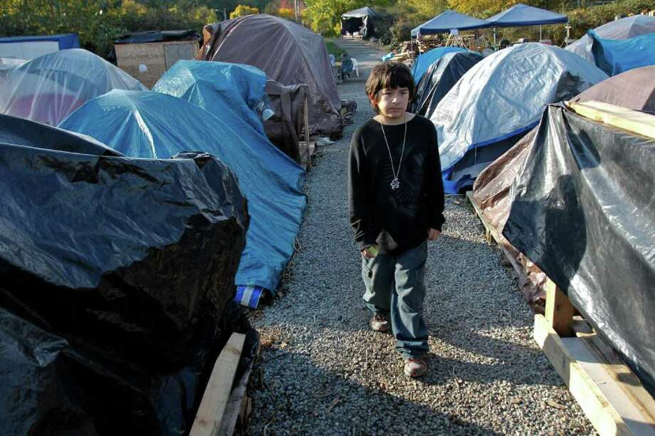 K'eet Dundas, 11, walks among the tents in the Nickelsville tent community in West Seattle on Saturday, Nov. 5, 2011. Over 130 people are housed here on any given day and as the weather gets colder many are struggling to stay warm. K'eet's mother Martina said its really cold and there needs to be more funding for families. She said there is almost always a place for a couple but there is not very much support for families that want to stay together. Currently there are at least four pregnant women living Nickelsville. Photo: JOE DYER / SEATTLEPI.COM