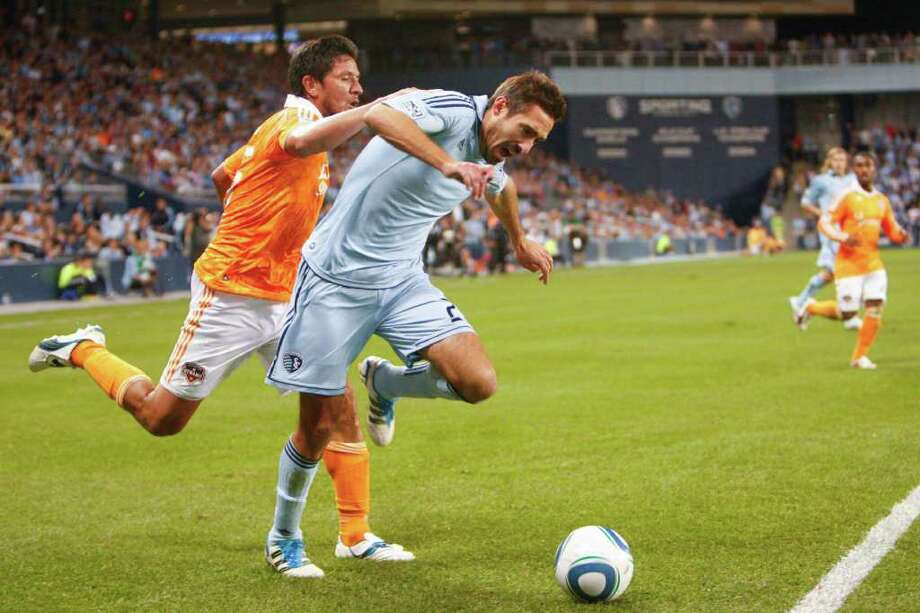 KANSAS CITY, KS - NOVEMBER 06:  Davy Arnaud #22 of the Sporting Kansas City is tripped by Brian Ching #25 of the Houston Dynamo in the second half during the MLS Eastern Conference Championship match at Livestrong Sporting Park on November 06, 2011 in Kansas City, Kansas. Photo: Kyle Rivas, Getty / 2011 Getty Images