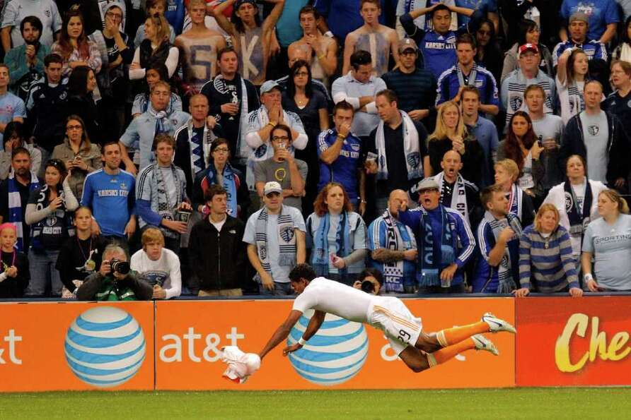 KANSAS CITY, KS - NOVEMBER 06:  Carlo Costly #29 of the Houston Dynamos slides in celebration after