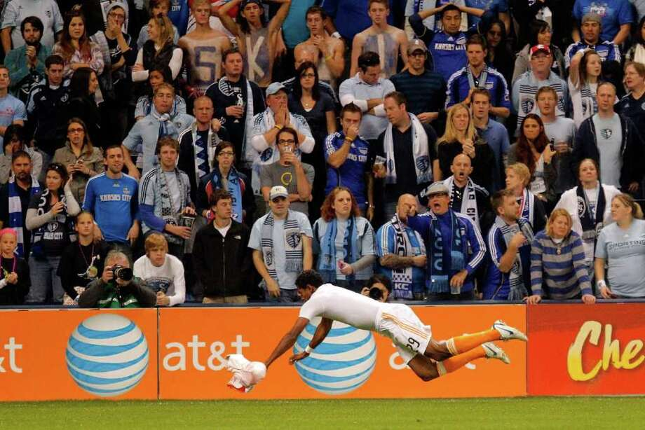 KANSAS CITY, KS - NOVEMBER 06:  Carlo Costly #29 of the Houston Dynamos slides in celebration after scoring the second goal against Sporting Kansas City in the second half during the MLS Eastern Conference Championship match at Livestrong Sporting Park on November 06, 2011 in Kansas City, Kansas. Photo: Kyle Rivas, Getty / 2011 Getty Images