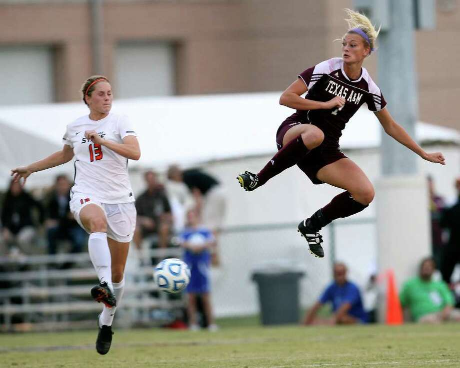 Oklahoma State University Carson Michalowski hustles for the ball against Texas A&M Annie Kunz in the 2011 Big 12 Soccer Championship game at Blossom Soccer Stadium, Sunday, Nov. 6, 2011. A&M won 1-0 in a last second goal. JERRY LARA/glara@express-news.net Photo: JERRY LARA, Express-News / SAN ANTONIO EXPRESS-NEWS