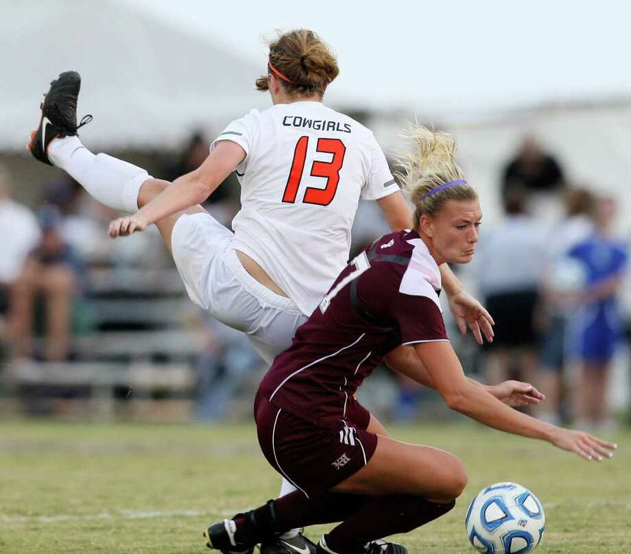 Oklahoma State University Carson Michalowski falls on top of Texas A&M Annie Kunz during the 2011 Big 12 Soccer Championship game at Blossom Soccer Stadium, Sunday, Nov. 6, 2011. A&M won 1-0 in a last second goal. JERRY LARA/glara@express-news.net Photo: JERRY LARA, Express-News / SAN ANTONIO EXPRESS-NEWS