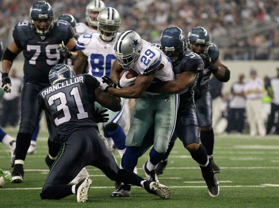 Dallas Cowboys running back DeMarco Murray (29) fights for extra yardage as Seattle Seahawks strong safety Kam Chancellor (31) and Leroy Hill, right, attempt to tackle during an NFL football game Sunday, Nov. 6, 2011, in Arlington, Texas. (AP Photo/Tony Gutierrez) Photo: Tony Gutierrez, Associated Press / AP