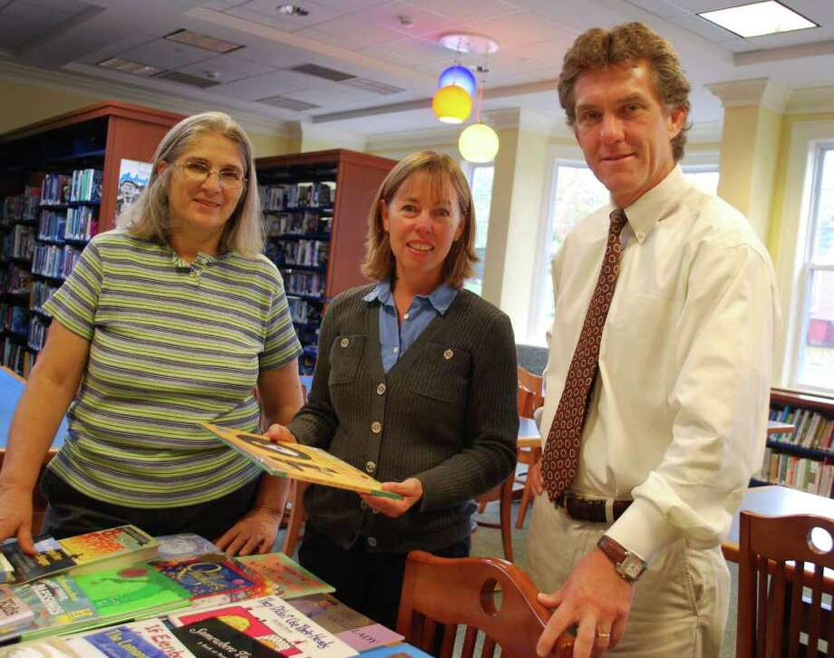 Mary Ann Lansdale, upper school librarian at New Canaan Country School; Cynthia Gorey, executive director of the New Canaan Community Foundation, and Tim Bazemore, head of New Canaan Country School; look over book titles. Photo: Contributed Photo