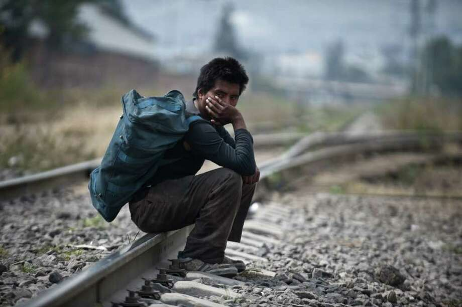 "A migrant sits on a train rail in Tultitlan, Mexico State, on November 7, 2011 moments before a group of 33 Central American women travelling in caravan across Mexico in search of migrant relatives passes by. The ""Caravan of mothers looking for their missing sons in transit"" has been following since November 1 the road mostly used by immigrants on their way to the United States. Photo: RONALDO SCHEMIDT, Getty / AFP"