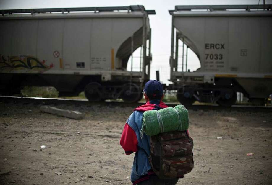 "A migrant walks towards a train in Tultitlan, Mexico State, on November 7, 2011 moments before a group of 33 Central American women travelling in caravan across Mexico in search of migrant relatives passes by. The ""Caravan of mothers looking for their missing sons in transit"" has been following since November 1 the road mostly used by immigrants on their way to the United States. Photo: RONALDO SCHEMIDT, Getty / AFP"