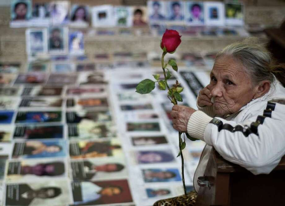 """One of the 33 Central American women travelling in caravan across Mexico in search of migrant relatives, sits next to portraits of their missing loved ones at a church in Tultitlan, city in Mexico State where they will spend the night at a refugee regularly used by immigrants, on November 7, 2011. The """"Caravan of mothers looking for their missing sons in transit"""" has been following since November 1 the road mostly used by immigrants on their way to the United States. Photo: RONALDO SCHEMIDT, Getty / AFP"""