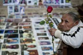 """One of the 33 Central American women travelling in caravan across Mexico in search of migrant relatives, sits next to portraits of their missing loved ones at a church in Tultitlan, city in Mexico State where they will spend the night at a refugee regularly used by immigrants, on November 7, 2011. The """"Caravan of mothers looking for their missing sons in transit"""" has been following since November 1 the road mostly used by immigrants on their way to the United States."""