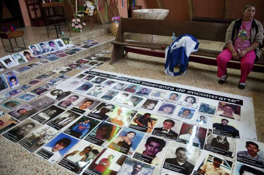 "One of the 33 Central American women travelling in caravan across Mexico in search of migrant relatives, sits next to portraits of their missing loved ones at a church in Tultitlan, city in Mexico State where they will spend the night at a refugee regularly used by immigrants, on November 7, 2011. The ""Caravan of mothers looking for their missing sons in transit"" has been following since November 1 the road mostly used by immigrants on their way to the United States. Photo: RONALDO SCHEMIDT, Getty / AFP"
