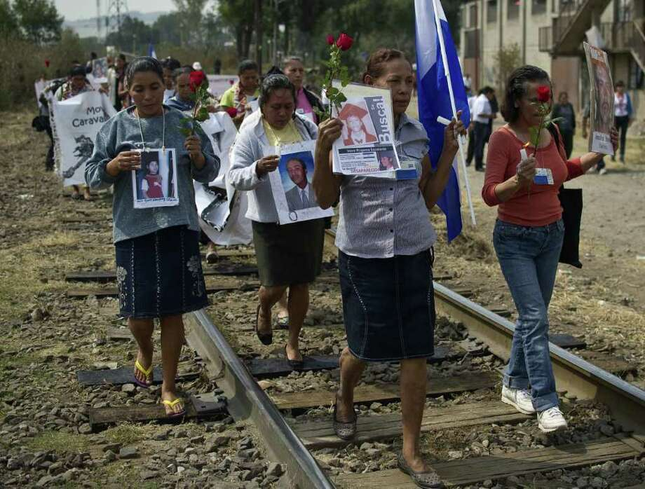 "A group of 33 Central American women travelling in caravan across Mexico in search of migrant relatives, hold a procession along a train rail in Tultitlan, city in Mexico State where they will spend the night at a refugee regularly used by immigrants, on November 7, 2011. The ""Caravan of mothers looking for their missing sons in transit"" has been following since November 1 the road mostly used by immigrants on their way to the United States. Photo: RONALDO SCHEMIDT, Getty / AFP"