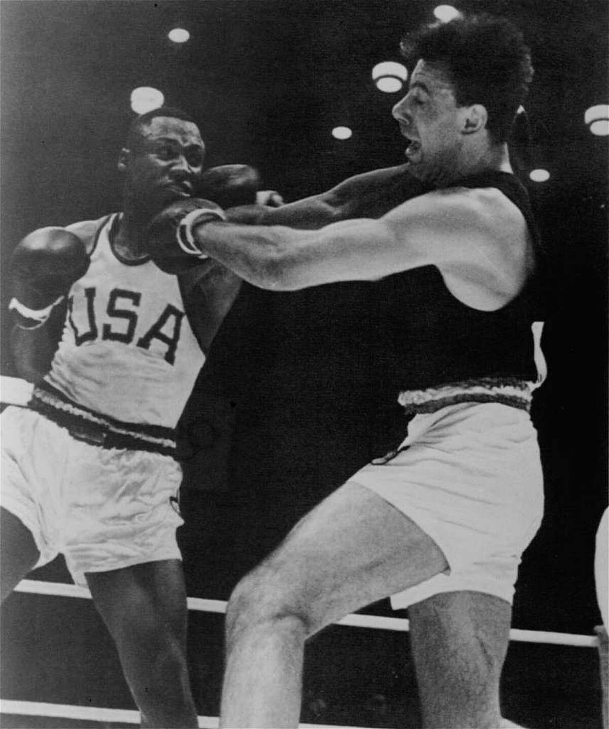 Frazier, left, throws a left to the head of Germany's Hans Huber in their Olympic title bout on Oct. 23, 1964 in Tokyo.