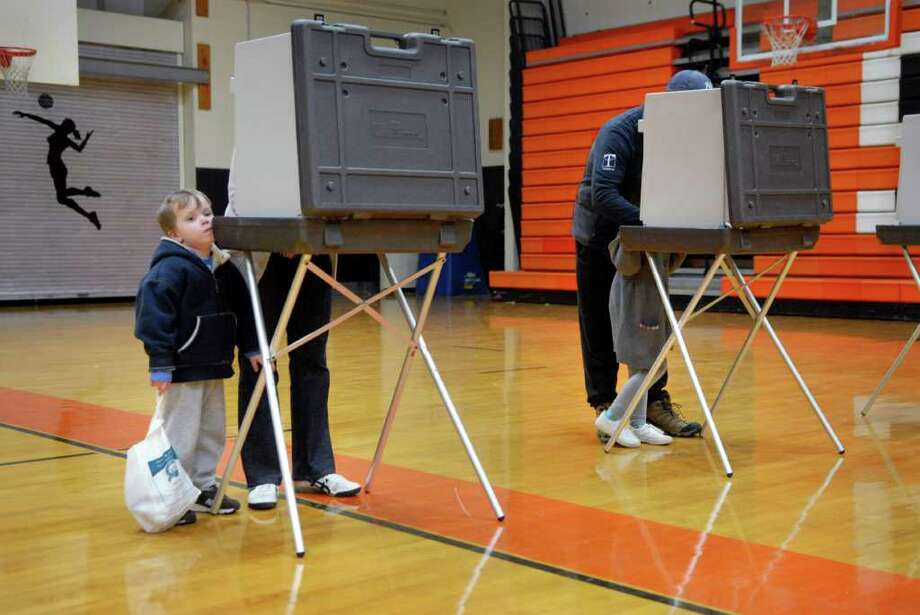 Charlie Reynols (4) waits for his mother Beth to vote, in the next booth his dad Mike shows sister Ruthie (6) how to fill out the ballot at Stamford High School in Stamford, Conn. on Tuesday November 8, 2011. Photo: Dru Nadler / Stamford Advocate Freelance