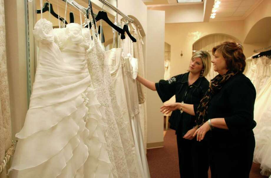 Starla Flake, right, owner of Brickhouse Bridal, checks some of the 50 designer wedding dresses for the Brides Across America giveaway with logistics manager Melanie Hensley. Photo: Lindsay Peyton