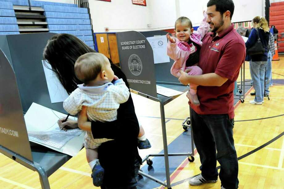 Peter Testa, right, holds daughter Sabine, 19 months, while his wife, Mary Ellen, votes on Election Day on Tuesday, Nov. 8, 2011, at Schenectady High in Schenectady, N.Y. Sabine waves at her brother Pellegrino, 6 months. The couple had to take turns between watching Sabine and voting. (Cindy Schultz / Times Union) Photo: Cindy Schultz / 00015307A